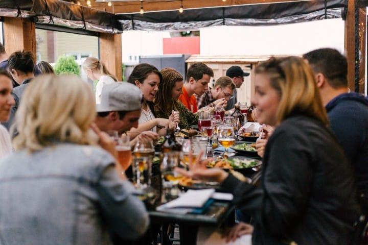 Personas comiendo. Foto: Priscilla Du Preez Tips para un viaje de negocios.
