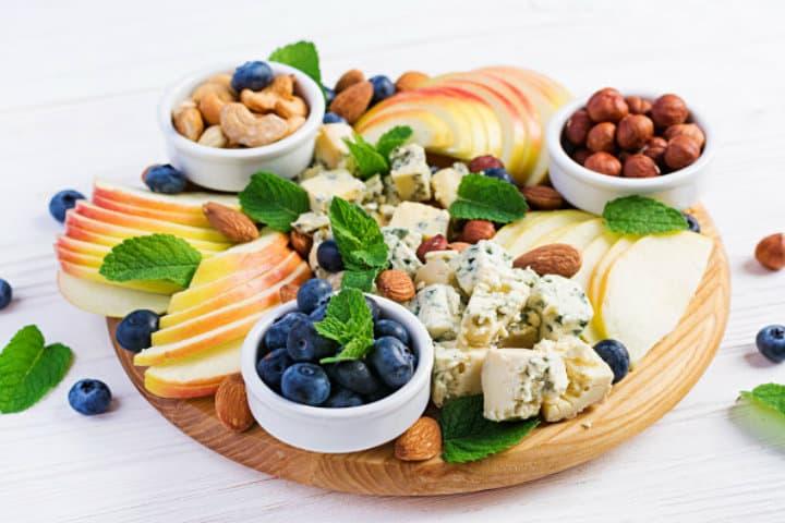 plato-quesos-variedad-quesos-arandanos-manzanas-nueces-mesa-blanca-plato-queso-italiano-fruta_2829-3824