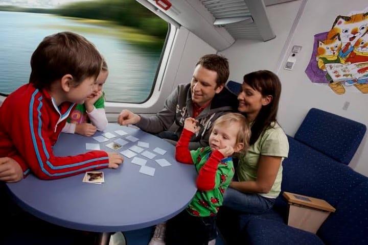 Familia jugando juegos de bolsillo en un viaje Foto Archivo