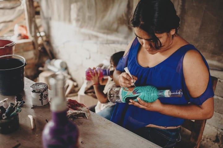 Manos artesanas oaxaqueñas se encargan de los diseños de las botellas de este mezcal Foto Mezcal Quiéreme Mucho | Facebook