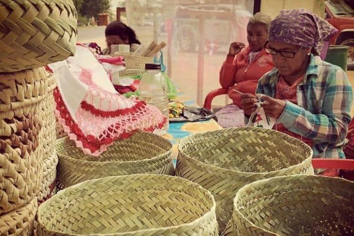 Mujeres bordando y tejiendo artesanías Foto: Archivo