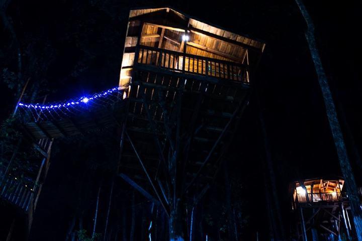 Cabaña alumbrada de noche. Foto Kali Tree Facebook