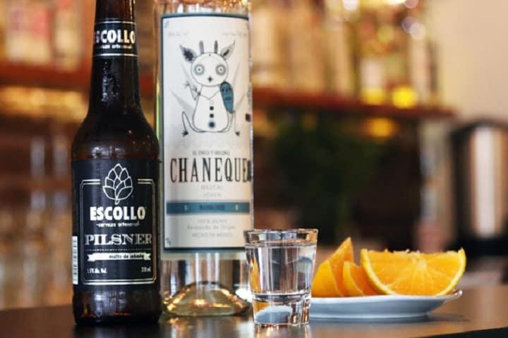 En Escollo podrás probar su cerveza artesanal y un buen mezcal acompañado de su naranja. Foto: Sopitas