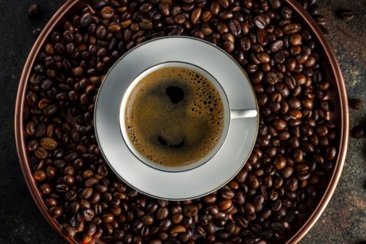 bandeja-redonda-cobre-granos-cafe-kopi-luwak-taza-cafe-blanca-platillo-sobre-superficie-oscura-vista-superior-primer-plano_128659-166